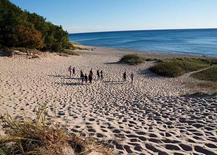 Students running down sand dune