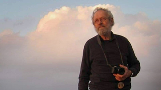 A man with a camera stares off into the distance with a cloud behind him.