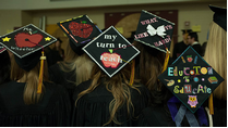 "Graduation caps with writing on them like ""Educated to Educate."""
