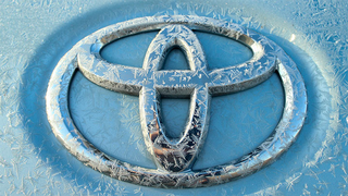 The Toyota logo with frost on it.