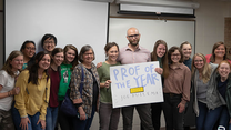 "A professor holds a sign that says ""Professor of the Year"" surrounded by students."