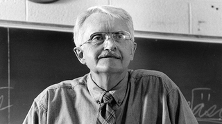 A black and white photo of an older professor with glasses in a classroom staring off to the right.
