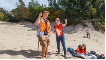 A professor and student wearing orange vests talking on a sand dune while doing field research.