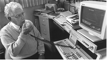 In a black and white photo, a man seated is speaking into an audiology device attached to a computer