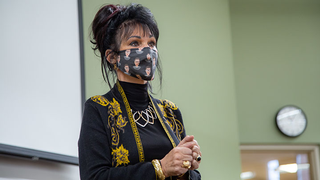 A woman stands in front of a whiteboard in a mask speaking to a classroom of students.