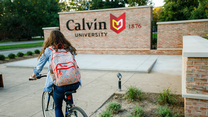 A student rides her bike near the Calvin University entrance sign.