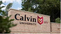 A  monument sign that says Calvin University located at the university's main entrance to campus