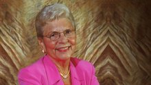 Headshot of a woman with gray hair in a pink blazer against a tan backdrop.