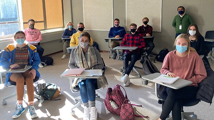 Class of high school students in masks sit in desks with college professor standing in back of room