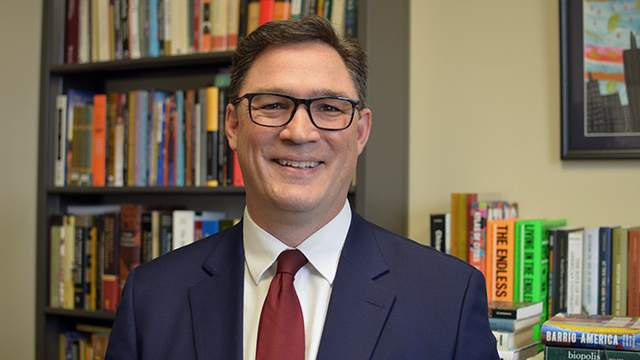 A man in a blue suit coat, white shirt, red tie wearing glasses and smiling in front of bookshelves.