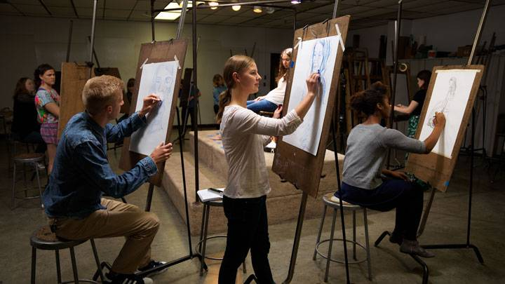 Students in art studio doing figure drawing
