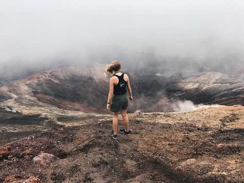 Student standing in front of volcano
