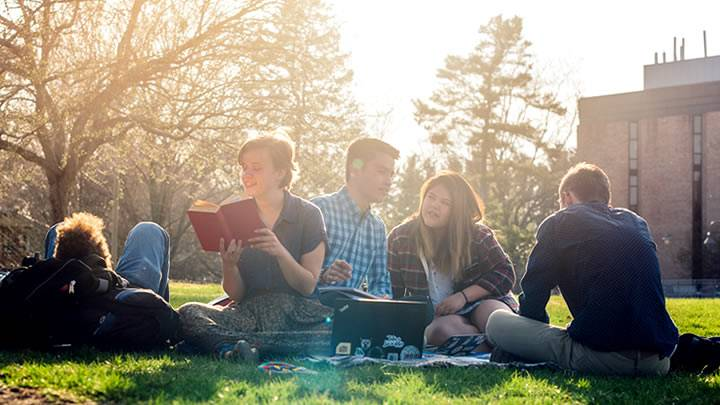 Students on the commons lawn, sun setting, smiling and chatting together, reading books.