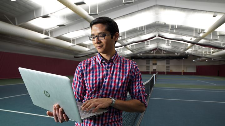 Male student with laptop in the Huizenga Tennis and Track Center