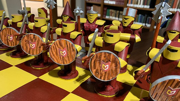 A row of chess pieces on a maroon and gold board with the Calvin logo on them.