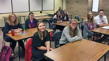 Nine smiling students sit at shared tables facing forward in a classroom.