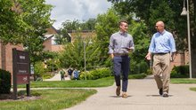 A student and a professor talk with each other as they walk on a campus path.
