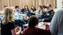 A professor, traditional college students, and adult learners sit in a circle engaged in discussion.