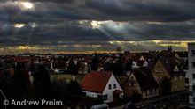 Sunlight shines through thick clouds onto a neighborhood in Germany