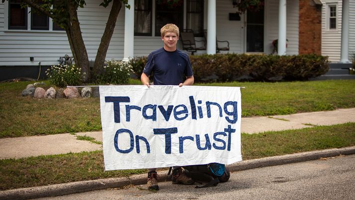 "Josh deLacy '13 holds up a banner that reads ""Traveling on Trust""."