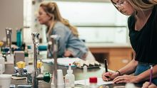 Two female students stand by and do work at a lab table.
