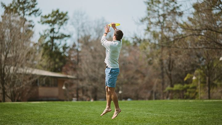 Student playing frisbee on Commons Lawn