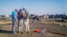 Three researchers use a surveying tripod on a hill in front of numerous ancient ruins.