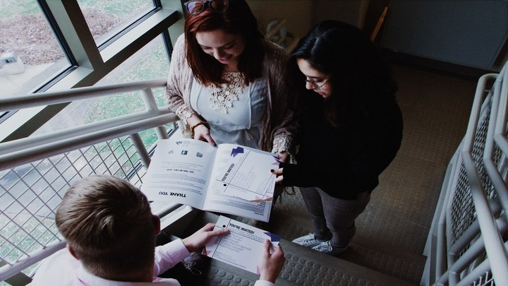 Three students are standing in a stair well talking while looking at papers they are holding