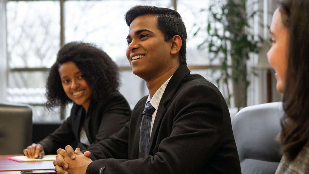 Students in professional clothing smiling, looking off into the distance
