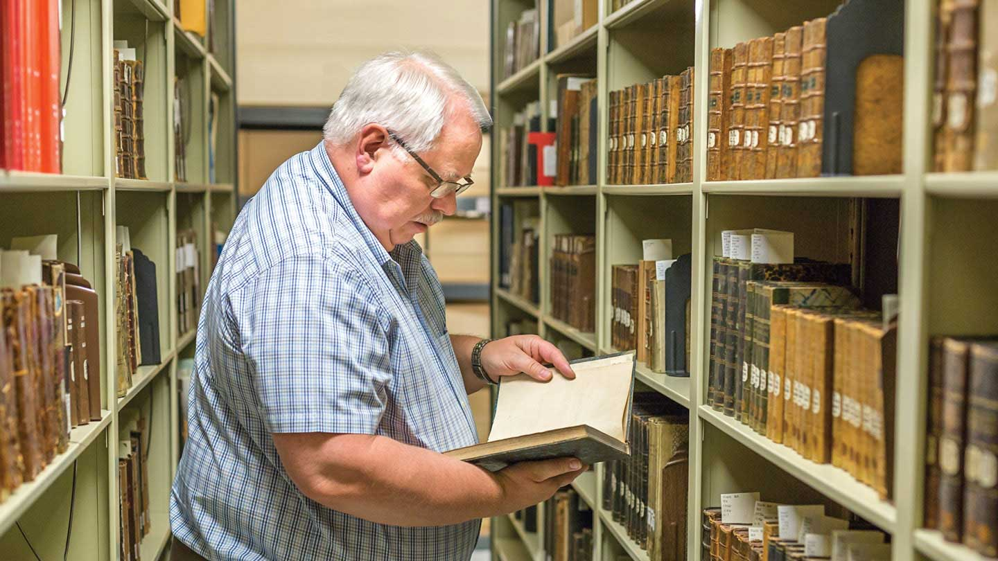 Dick Harms inspecting a book in the archives.