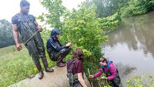 Students and professor in waders take a water sample from a pond in the rain.