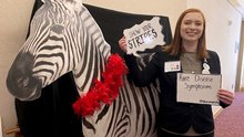 A female college student in a suit coat stands next to a Zebra cutout.