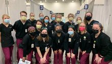 About a dozen nurses in scrubs and masks pose for a photo at an indoor COVID-19 vaccination clinic.