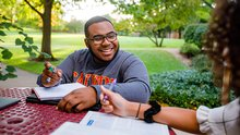 On a fall day,  a student smiles as he sits at a table outside across from two fellow students.