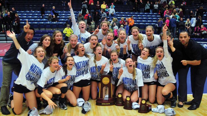The Calvin women's volleyball team posing joyously with a trophy.