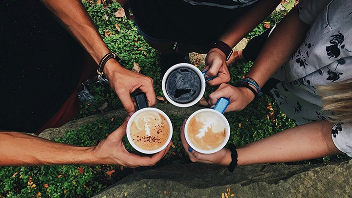 Three people hold full coffee mugs together in triangle above grass.