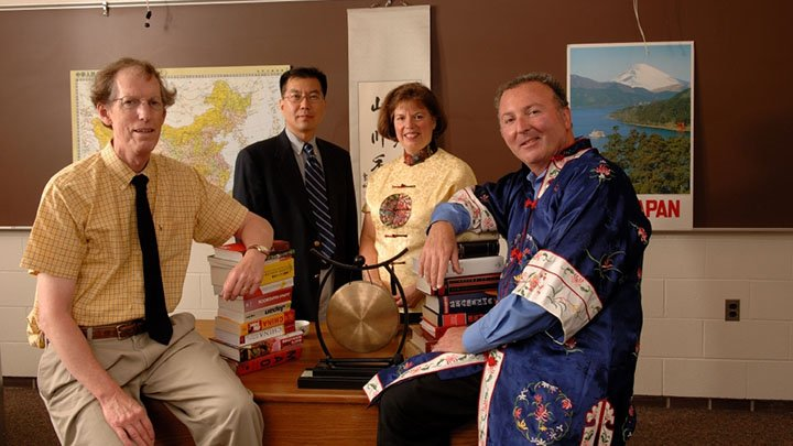 Four Asian Studies faculty members pose together in a classroom.