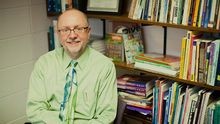 A male professor in a shirt and tie smiles sitting in front of his office bookshelf.