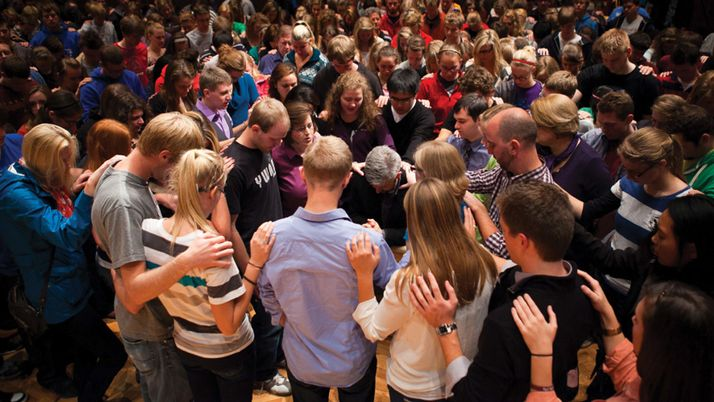 Members of the Calvin College community lay hands on Michael Le Roy in prayer.