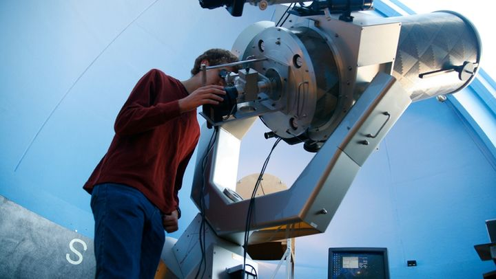 Color photo of student handling observatory telescope