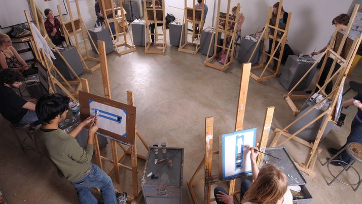 Students painting on easels in an art studio at Calvin.
