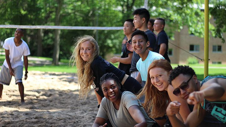 Students by the residence hall outdoor volleyball court, excited and smiling