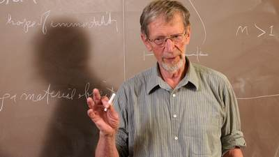 Alvin Plantinga in front of a chalkboard.