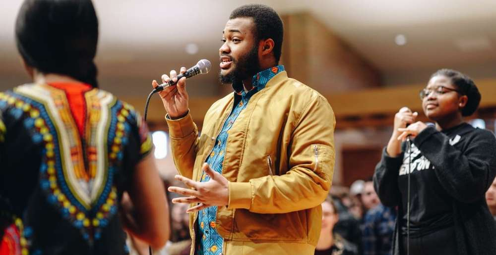 Male Calvin University student of color speaking at a microphone in the Calvin chapel