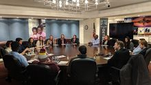 Students and city leaders meet around a roundtable.