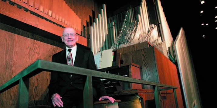 Hamersma pictured beside the Fine Arts Center organ in 2006, when he delivered a January Series lecture on organ music.
