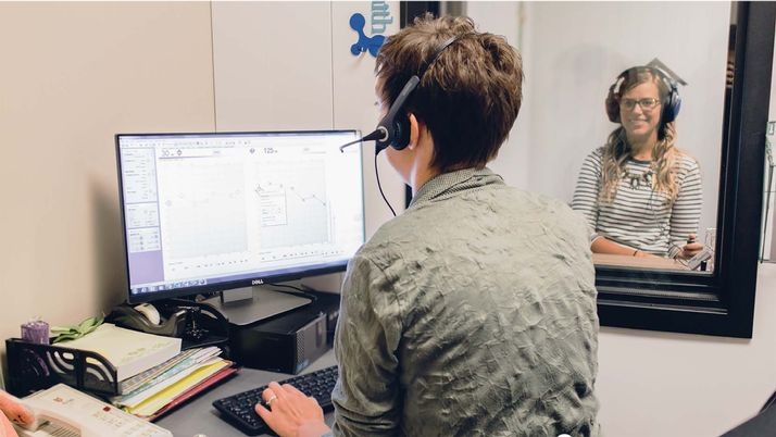 A person wearing headphones studies a computer screen with data while another looks on behind glass.