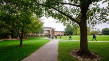 A wide shot of students walking on the path near the Commons Lawn at Calvin University.