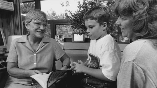 A middle-aged woman holding a book sitting and talking with a child and his mother.