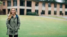 Student in a green coat standing outside smiling for the camera.